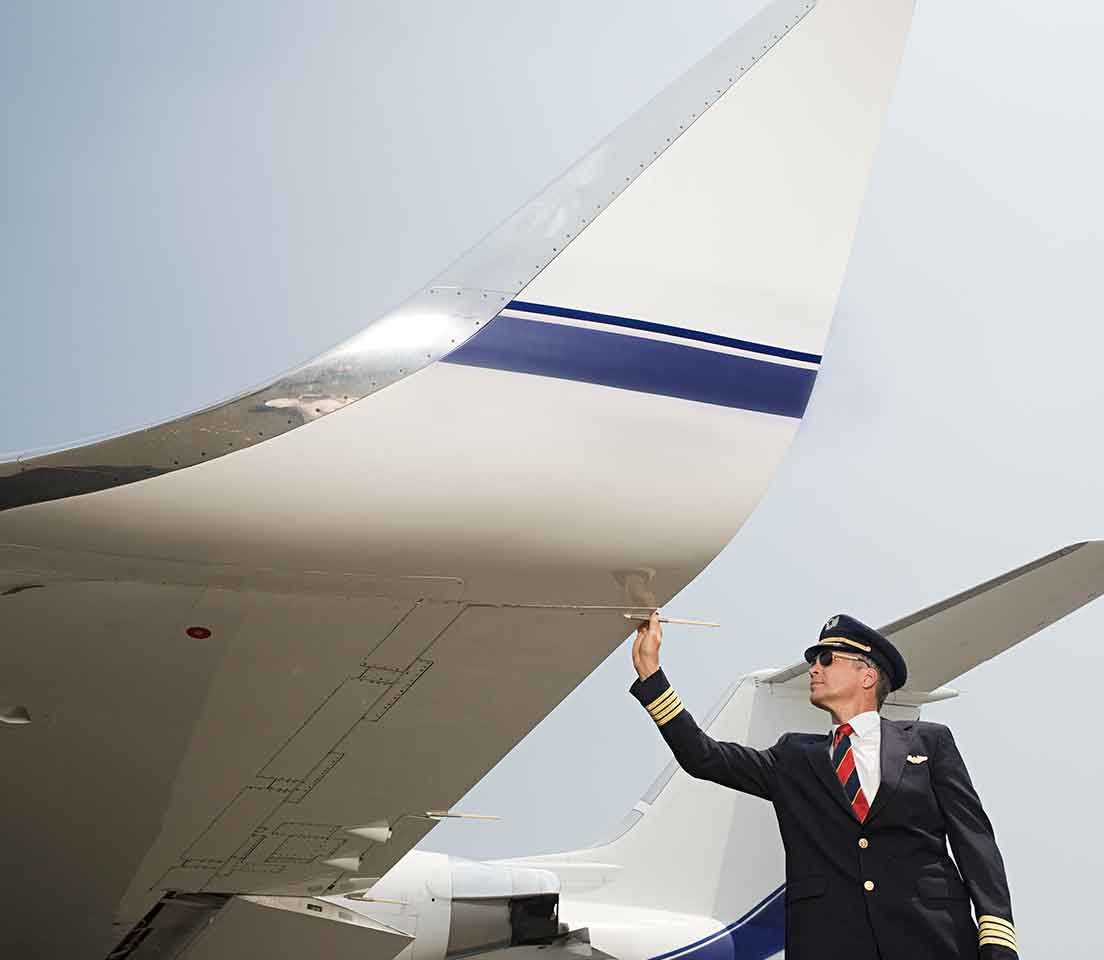 A pilot inspects the wing of his aircraft before takeoff.
