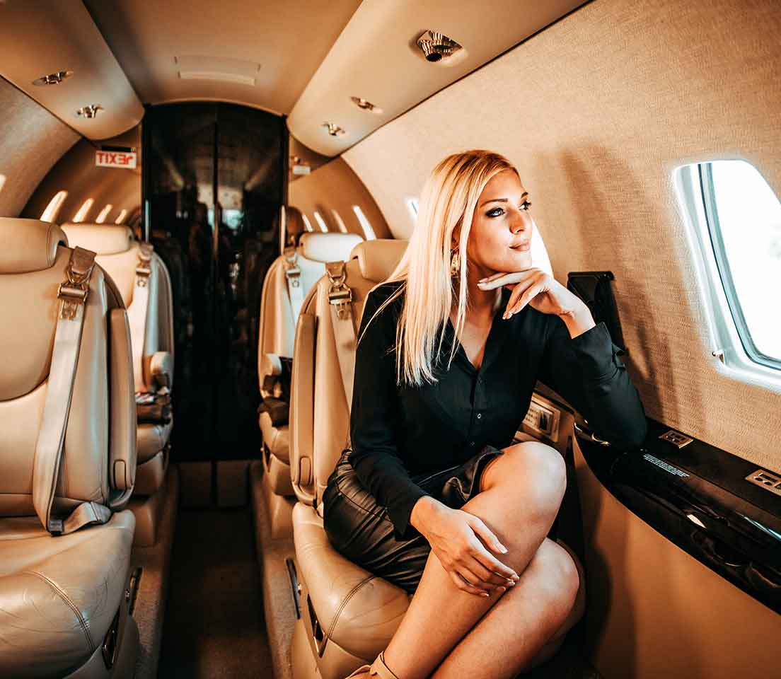 Young woman seated in a private jet.